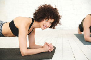 Smiling fitness woman planking on an exercise mat and looking at camera in a gym