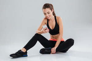 Smiling fitness woman sitting on the floor and using smartphone over gray background