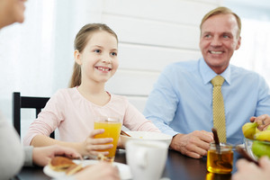 Smiling girl and her father sitting by table by breakfast
