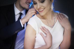 Smiling man giving woman elegant necklace