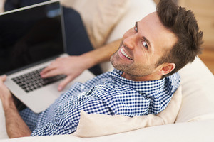 Smiling man using computer in living room