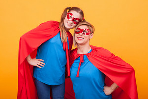 Smiling mother and daughter dressed like heroins bonding over yellow background. Superhero costume. Happy kid. Great childhood.