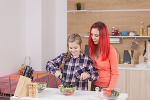 Smiling mother preparing salad with her daughter. Little helper