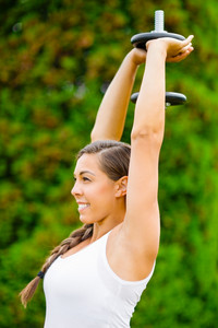 Smiling Pregnant Woman Doing Triceps Extension Exercise In Park