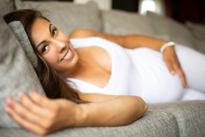 Smiling pregnant woman lying on the sofa with her hand at belly