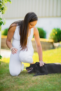 Smiling pregnant woman with a big belly pats her dog in the garden