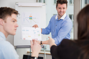 Smiling Professional Showing Chart To Colleagues