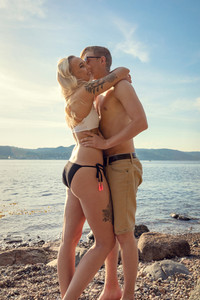 Smiling romantic couple in embrace at the beach