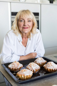Smiling seniorwoman leaning on a table with baking tray tray full of muffins at the kitchen