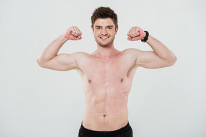Smiling shirtless sportsman showing biceps and looking at camera isolated over white
