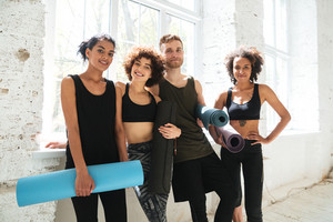 Smiling team of healthy people looking camera after training and holding training mats