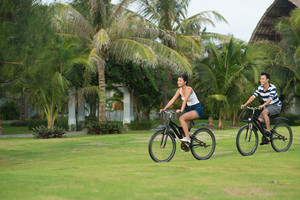 Smiling Vietnamese couple riding on bikes in the park: health lifestyle concept