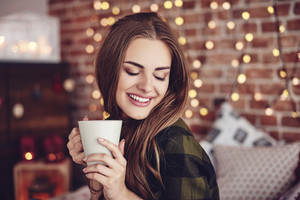 Smiling woman drinking coffee at home