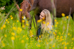 Smiling woman sits in the meadow with her beautiful arabian horse