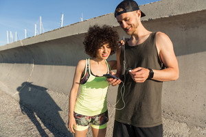 Smiling young fitness couple listening to music with earphones outdoors together