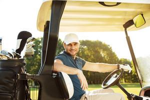 Smiling young male golfer sitting in a golf cart and looking at camera