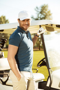 Smiling young male golfer standing at the golf cart and looking at camera