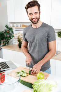 Smiling young man preparing vegetable salad in the modern guy