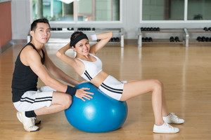 Smiling young woman doing sit-ups on a fitness-ball with the help of her personal trainer