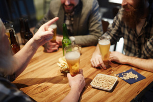 Snack and beer on table and hands of men during talk