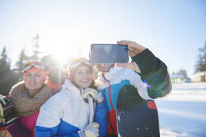 Snowboarders taking selfie on the hill