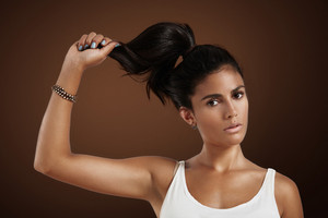 spanish woman hold her hair in hand watching at camera. hair strenght concept