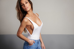 spanish woman in studio shoot wears swimsuit and jeans