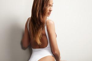 spanish woman in studio shoot wears white swimsuit