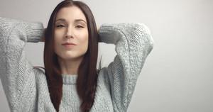 spanish woman sreaching and touching her straight dark hair. ideal skin portrait