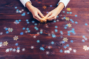 Sparkler in female hands and decorative snowflakes on the table, top view