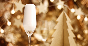 Sparkling wine in a flute glass on the background of stylish Christmas decorations in golden tones