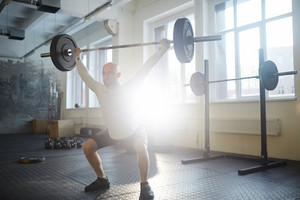 Sportsman squatting while lifting heavy barbell