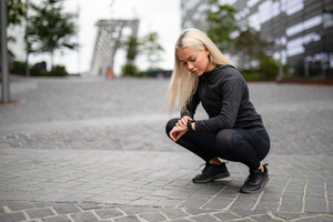 Sporty Female Runner Using Smartwatch to See Running Performance