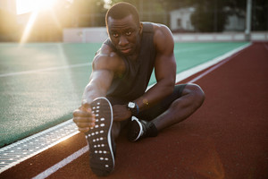 Sporty muscular african male athlete stretching legs while sitting at the stadium race track