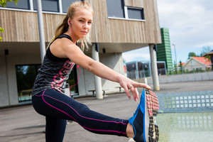 Sporty Woman Stretching Hamstring Leg Muscles Outdoors