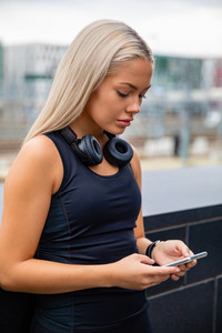 Sporty Woman Text Messaging Using Smartphone On Bridge