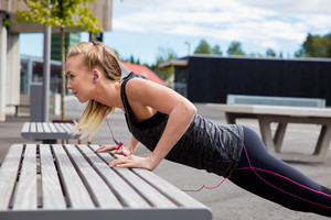 Sporty Young Woman Doing Pushups On Bench In Park