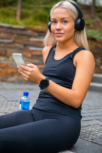 Sporty Young Woman Listening Music With Headphones And Smartphon