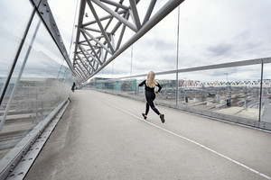 Sporty young woman running fast in city environment