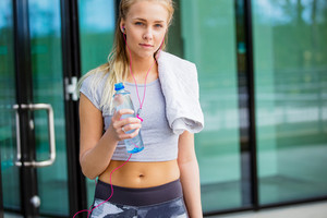 Sporty Young Woman With Water Bottle And Napkin Outdoors