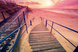 Stairway to the sandy beach at sunset
