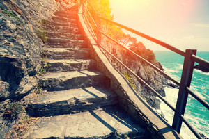 Stairways in rock over sea at sunset. The Way of Love Via dell'Amore in Cinque Terre, Italy