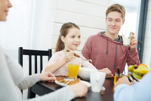 Starting new day in bosom of family: pretty little girl eating cornflakes, her teenage brother drinking milk and looking at her with slight smile