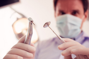 Stomatologist holding dental tools, view from the perspective of a patient