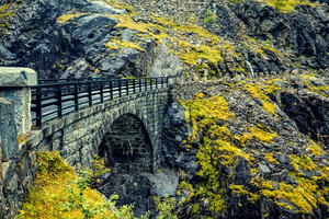 Stone bridge above Stigfossen waterfall in mountains. Trollstigen, Trolls Path, Norway
