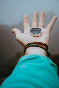 Stretched man arm with compass on the palm of the hand directed to mountain peaks on cloudy day