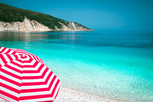 Striped red sun beach umbrella on a pebble beach with turquoise blue sea, white rocks and sky in background