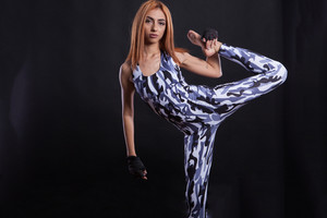 Studio fitness photoshoot with girl having great flexibilty on black background. Performance and discipline.