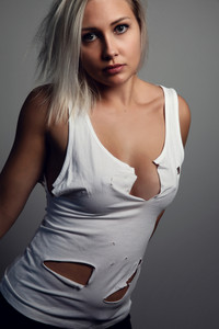 Studio portrait of beautiful blonde woman with worn holey t-shirt