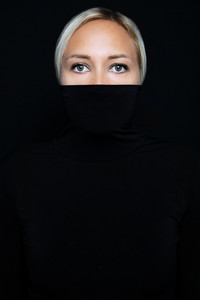 Studio portrait of beautiful elegant woman hiding face in black turtleneck